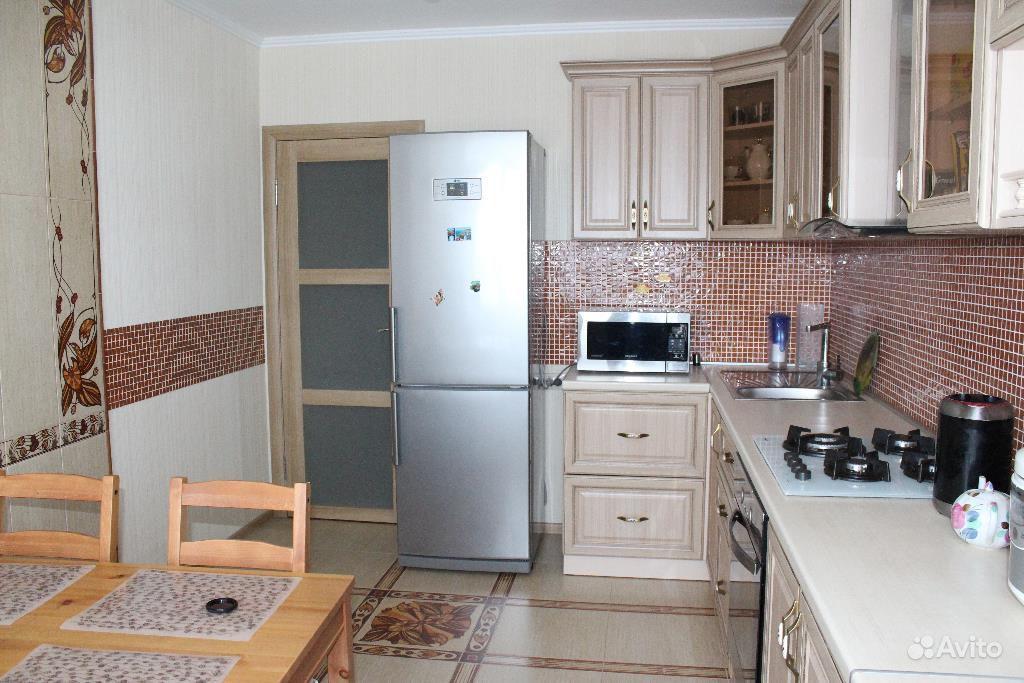 Интерьер кухни с холодильником у двери